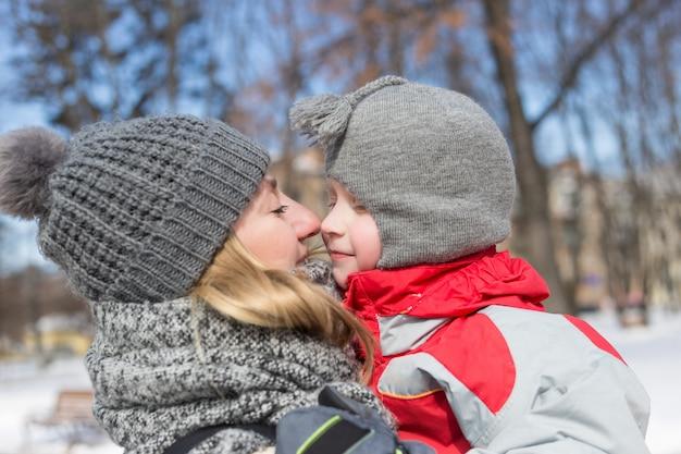 Giovane madre felice e suo il bambino nel parco in inverno