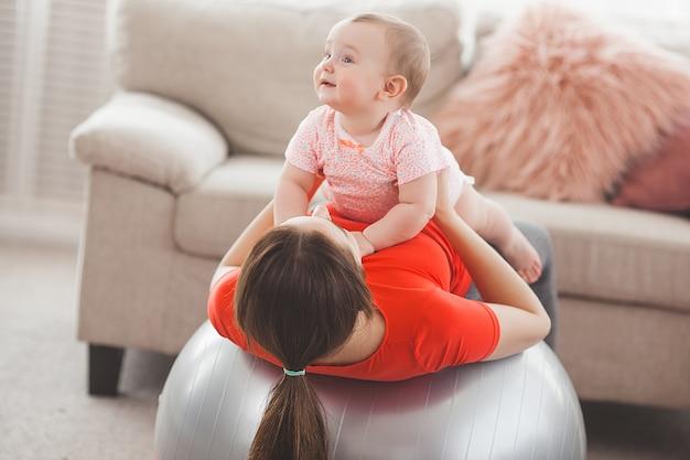 Giovane madre graziosa che risolve con il suo piccolo bambino a casa