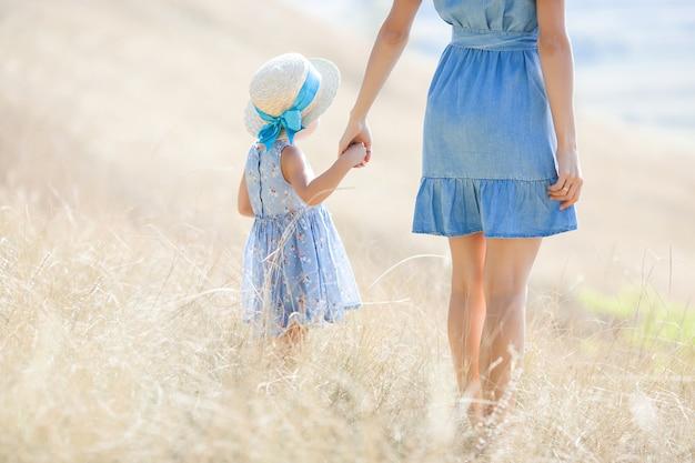Giovane madre graziosa e sua figlia all'aperto. ritratto del primo piano della famiglia felice sul campo naturale selvaggio. le ragazze si divertono.