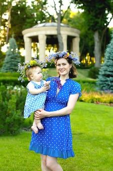 Giovane madre in un vestito blu con pois e una corona di fiori di campo che tiene il bambino tra le braccia.