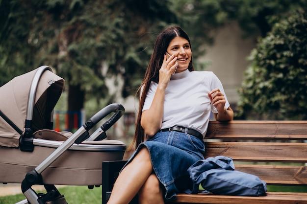 Giovane madre seduta su una panchina nel parco con passeggino