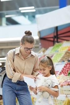 Giovane madre shopping nel mercato degli agricoltori