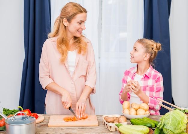 Giovane madre sorridente e sua figlia che preparano la verdura sul tagliere