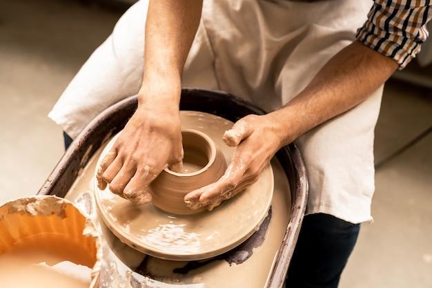 Giovane maestro contemporaneo della ceramica seduto ruotando la ruota mentre si plasma la pentola dall'argilla liquida in officina