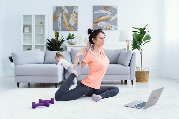 Giovane mamma adorabile divertendosi a praticare la meditazione rilassante nel fine settimana senza stress con la bambina.