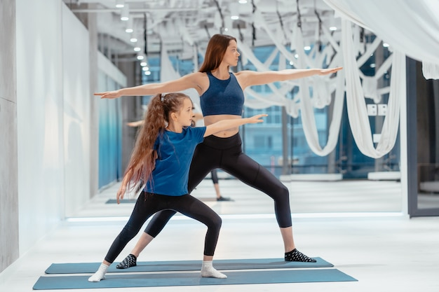 Giovane mamma adulta e piccola figlia insieme sull'aerobica