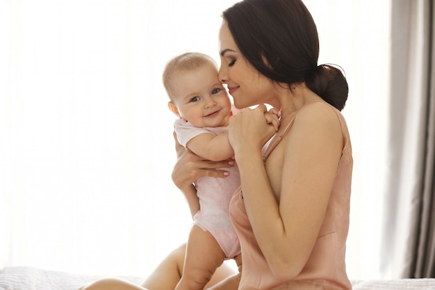 Giovane mamma attraente in indumenti da notte sorridente che abbraccia baciando il suo bambino seduto nel letto sopra la finestra occhi chiusi.