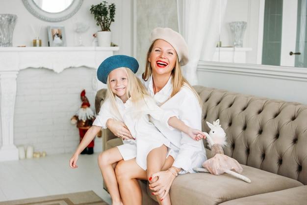 Giovane mamma divertente felice capelli lunghi biondi e ragazza carina divertirsi insieme in salotto, stile di vita famiglia felice