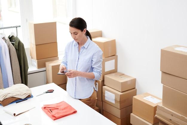 Giovane manager dell'ufficio del negozio online che cattura foto del pullover rosso piegato sullo smartphone durante il lavoro