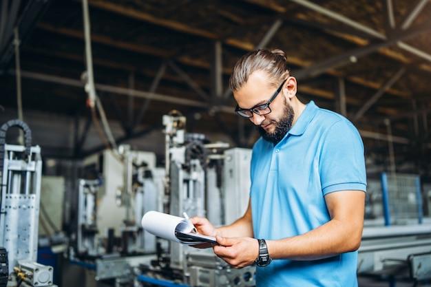 Giovane manager ingegnere con la barba che controlla manifattura, posto di lavoro e macchinari in grande fabbrica.