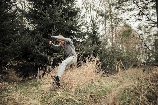 Giovane maschio atletico che salta sopra l'erba mentre addestramento di sport