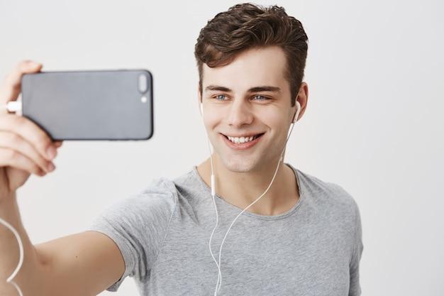 Giovane maschio caucasico bello con capelli scuri e gli occhi azzurri attraenti che tengono telefono cellulare, posando per il selfie, guardante con il sorriso civettuolo. bel ragazzo che fa una videochiamata.