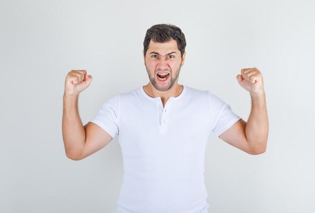 Giovane maschio che grida ad alta voce con i pugni chiusi in maglietta bianca e sembra emotivo