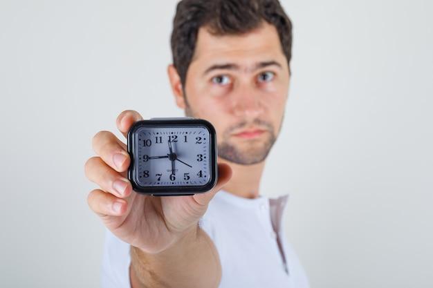 Giovane maschio che indica orologio alla macchina fotografica in maglietta bianca