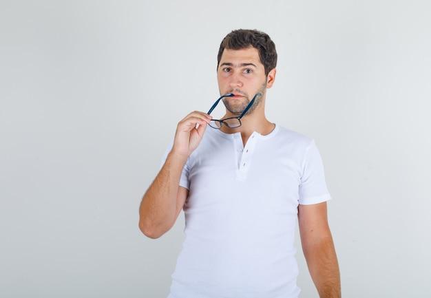 Giovane maschio che morde leggermente i suoi occhiali in maglietta bianca e sembra pensieroso