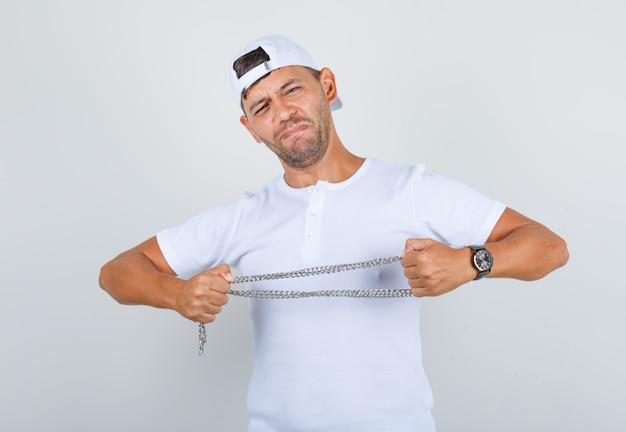 Giovane maschio che tira la catena del metallo in maglietta bianca, cappuccio, vista frontale.