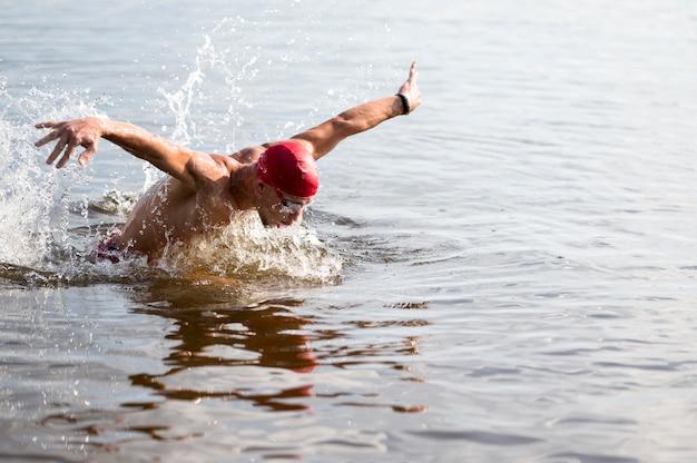 Giovane maschio con cappuccio rosso nuotare nel lago