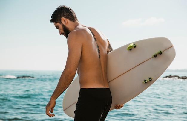 Giovane maschio con tavola da surf vicino oceano