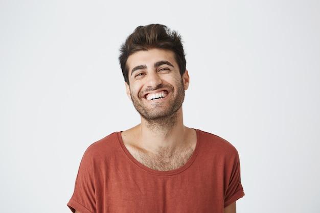 Giovane maschio dalla pelle scura attraente con la barba lunga in maglietta rossa che sorride ampiamente ridendo dell'immagine divertente su internet. espressioni facciali ed emozioni positive
