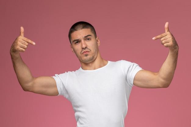 Giovane maschio di vista frontale in camicia bianca che posa appena con l'espressione del dito su fondo rosa