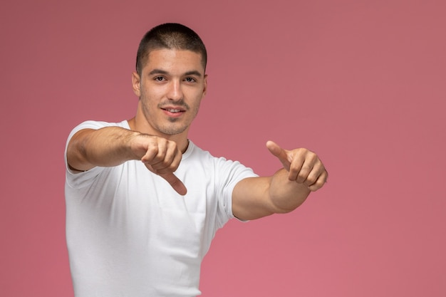 Giovane maschio di vista frontale in camicia bianca che posa con il dito alzato su fondo rosa