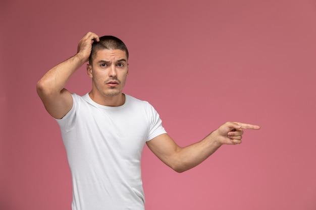 Giovane maschio di vista frontale in camicia bianca che posa con l'espressione esitante su fondo rosa