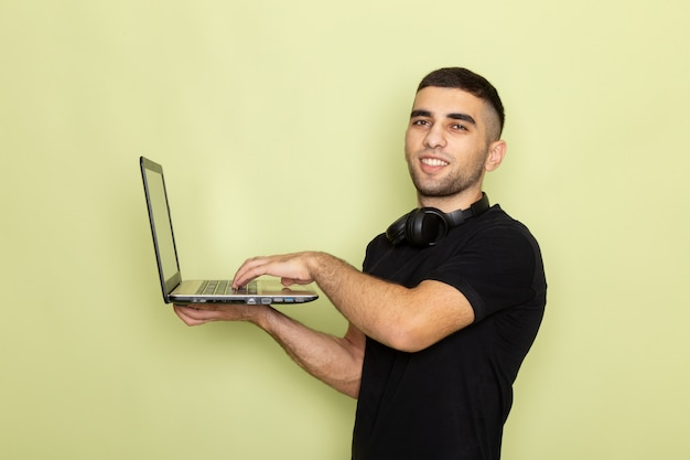 Giovane maschio di vista frontale in maglietta nera che sorride e che utilizza computer portatile sul verde