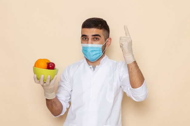 Giovane maschio di vista frontale in vestito bianco che indossa maschera e guanti che tengono piatto con frutti sul beige
