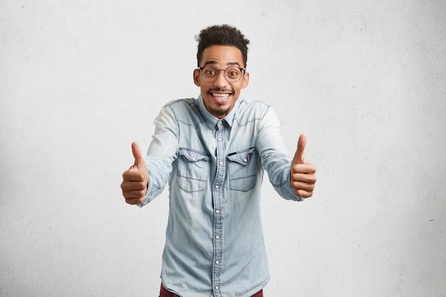 Giovane maschio felicissimo con capelli arruffati, baffi, alza i pollici, mostra un segno ok, è delizioso con i risultati degli esami di ammissione,