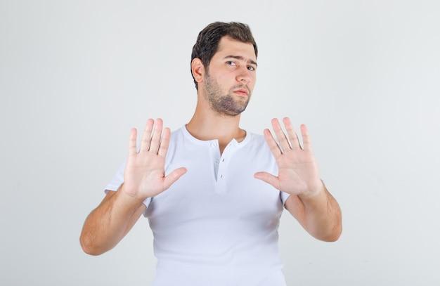 Giovane maschio in maglietta bianca che non mostra alcun segno e che sembra disgustato