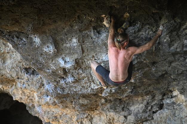 Giovane maschio scalatore bouldering una parete di roccia in una grotta