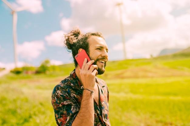 Giovane maschio sorridente che comunica sul telefono in prato