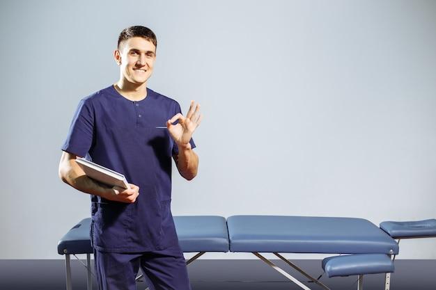 Giovane massaggiatore felice in uniforme, la rivista per il record nelle mani vicino al lettino da massaggio