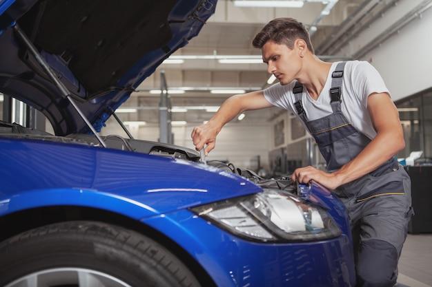 Giovane meccanico di automobile bello che ripara veicolo nel suo garage