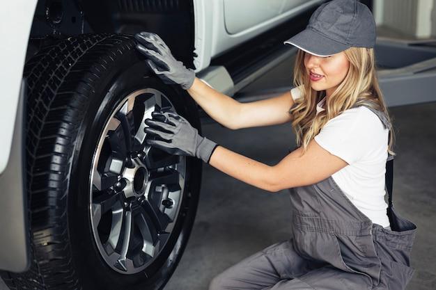 Giovane meccanico femminile ad alto angolo di lavoro