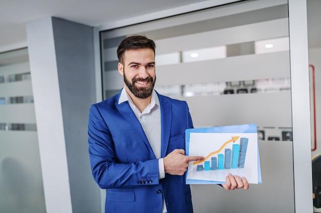 Giovane mediatore sorridente di successo in piedi nella hall della sua azienda, tenendo il grafico e indicandolo.