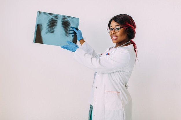 Giovane medico afroamericano della donna nell'abbigliamento medico che esamina immagine dei raggi x