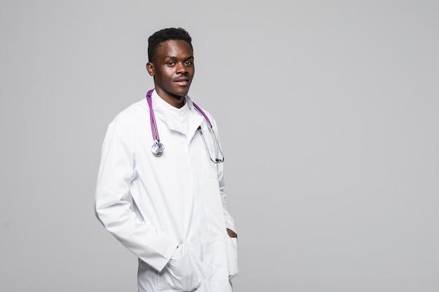 Giovane medico afroamericano in uniforme bianca isolato su sfondo bianco in piedi con le braccia in tasca che sembra professionale e altamente competente nel campo della specializzazione medica
