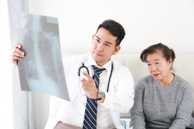 Giovane medico asiatico che parla con la donna senior in ospedale