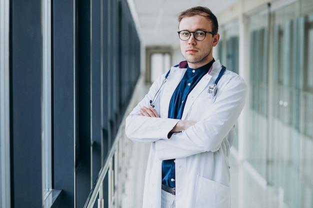 Giovane medico bello con lo stetoscopio alla clinica