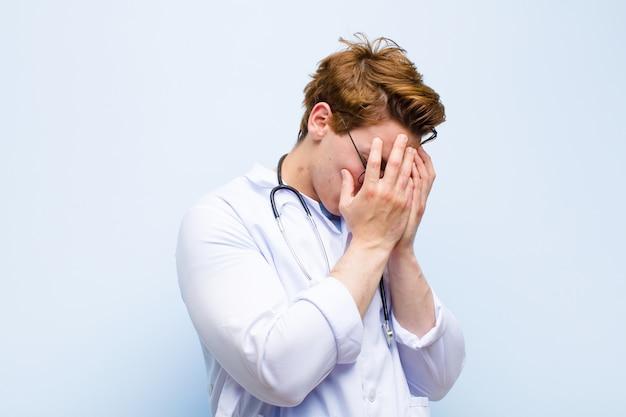 Giovane medico capo rosso che copre gli occhi con le mani con uno sguardo triste e frustrato di disperazione