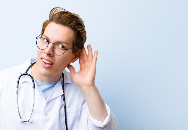 Giovane medico capo rosso che sembra ascolto serio e curioso che prova a sentire una conversazione segreta o un pettegolezzo che ascolta di nascosto contro la parete blu