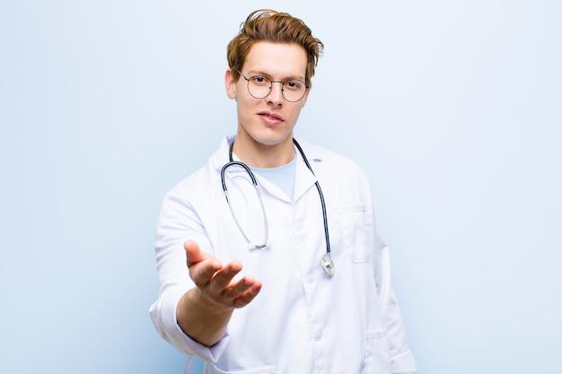 Giovane medico capo rosso che sorride, che sembra felice, sicuro e amichevole, offrendo una stretta di mano per chiudere un affare, cooperando contro il blu