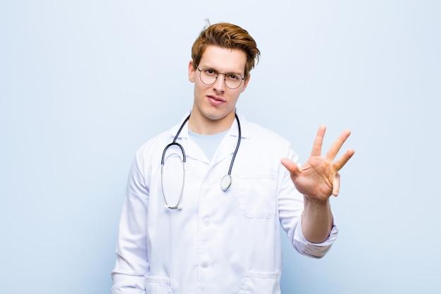 Giovane medico capo rosso che sorride e che sembra amichevole, mostrando numero quattro o quarto con la mano in avanti, conto alla rovescia contro la parete blu