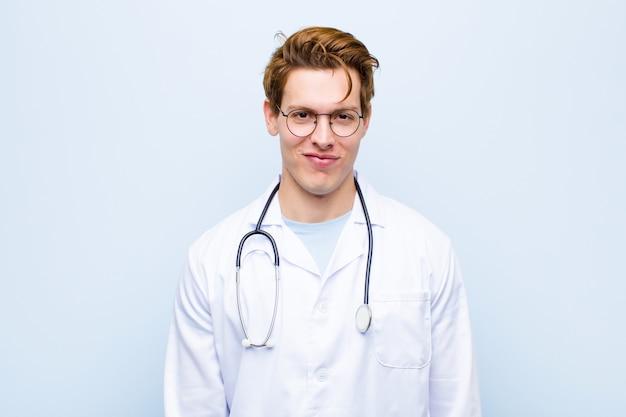 Giovane medico capo rosso che sorride positivamente e con confidenza, sembrando soddisfatto, amichevole e felice sulla parete blu