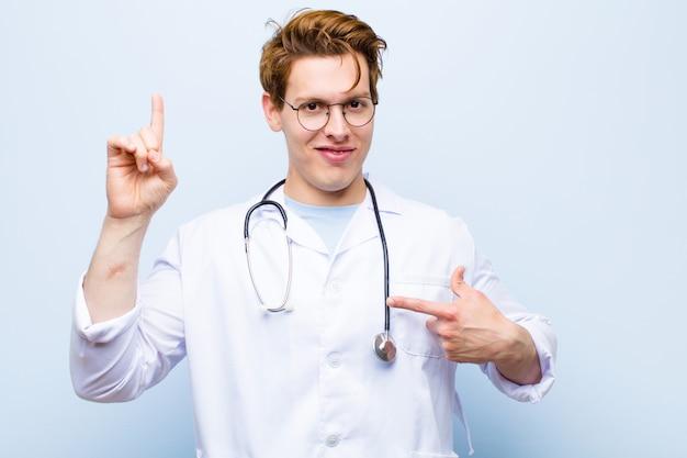 Giovane medico capo rosso sentirsi orgoglioso e sorpreso, indicando con fiducia se stesso, sentendosi come il numero uno di successo contro la parete blu