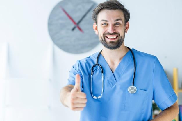 Giovane medico che gesturing pollice in su