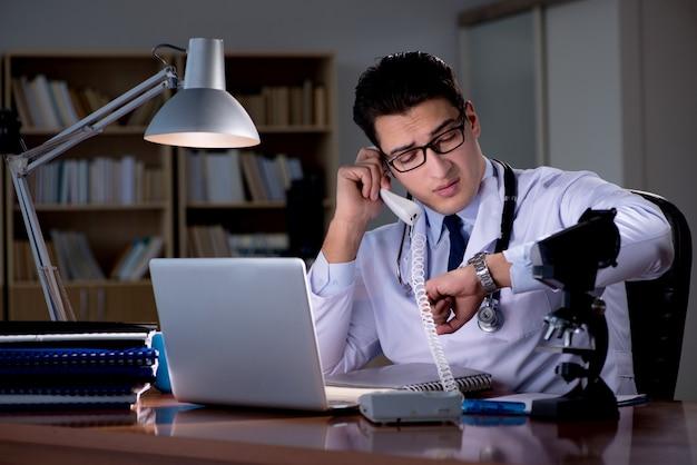 Giovane medico che lavora fino a tardi in ufficio