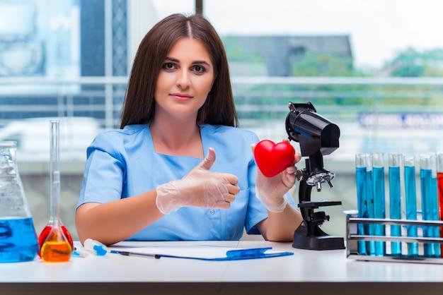 Giovane medico con cuore rosso in laboratorio