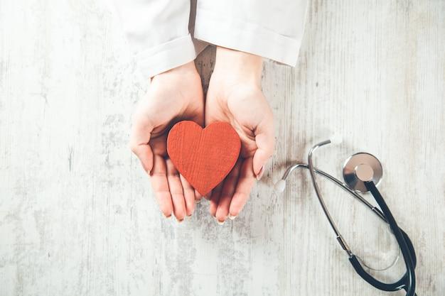 Giovane medico con il simbolo del cuore rosso seduto alla scrivania